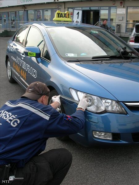 Rendőrök helyszínelnek egy XV. kerületi parkolóban, ahol megtalálták a taxit. (Fotó: Mihádák Zoltán)