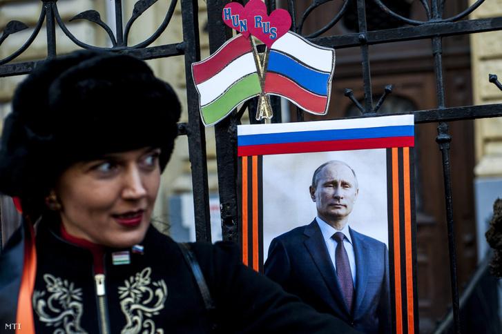 Egy résztvevő Vlagyimir Putyin portréja előtt az orosz elnök budapesti látogatása alkalmából tartott szimpátiatüntetésen Oroszország budapesti nagykövetségnél 2015. február 17-én.