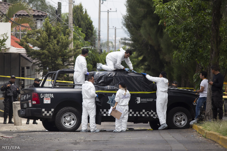 Helyszínelő rendőrök egy rendőrautó körül 2018. szeptember 3-án, miután egy fegyveres csoport megölt négy rendőrt a mexikói Tonalában.