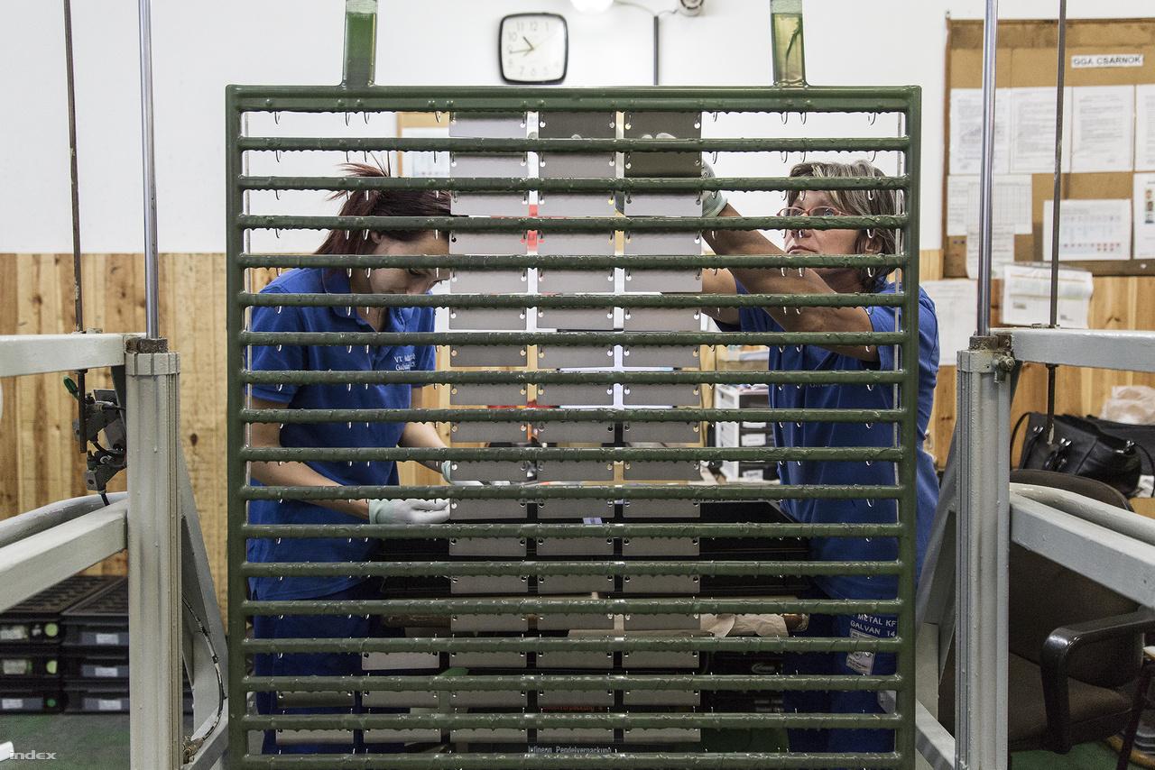 Két dolgozó szedi a szárítóról a bevonattal ellátott alkatrészeket.