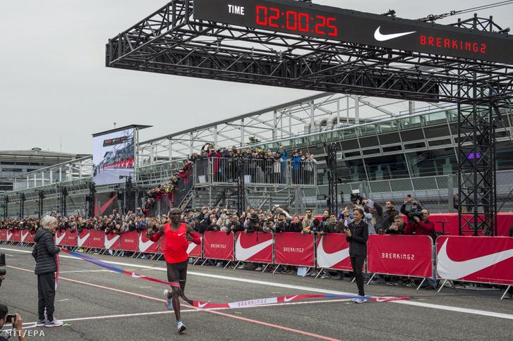 Eliud Kipchoge miután átszakította a célszalagot a 42 kilométeres maratoni távot két órán belül teljesítendő rekordkísérleten a monzai Forma-1-es versenypályán 2017. május 6-án.