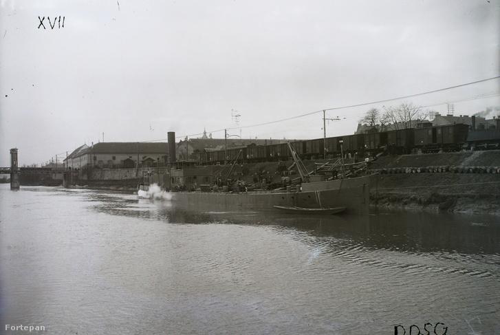 Áruszállító hajó az óbudai Duna-ágon, háttérben a Remmel-híd, a Zichy-kastély és egy tehervonati szerelvény a HÉV vágányain. Leltári jelzet: MMKM TFGY 2017.2.171.