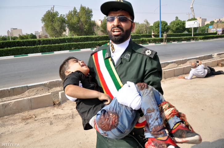 Sebesült gyermeket visz egy katona a délnyugat-iráni Ahváz városában ahol ismeretlen fegyveresek tüzet nyitottak és több ember lelőttek egy katonai parádén 2018. szeptember 22-én. A terrorcselekménynek több sebesültje is van.