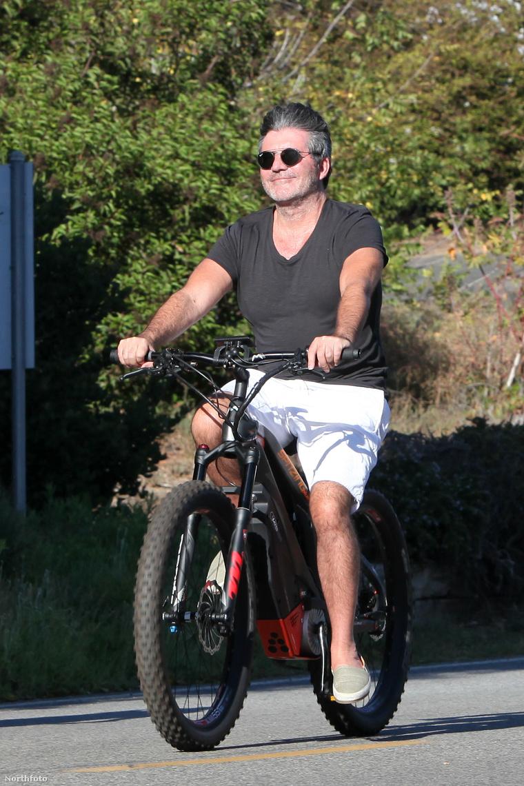 Simon Cowell elégedett arccal teker.