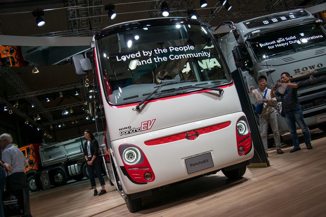 A rajzfilmfigura-arcú Poncho EV elektromos busz a japán Hino Motors terméke. A cég a Toyota leányvállalata, egyben az első hibrid teherautó gyártója is. A kisbuszt érdekessége a töltési koncepció: 10 km-enként az útba épített nagyfrekvenciás töltő tölti a járművet, vagyis nem kell egy töltőpontnál ácsorognia. Csak Japánban fogják árulni