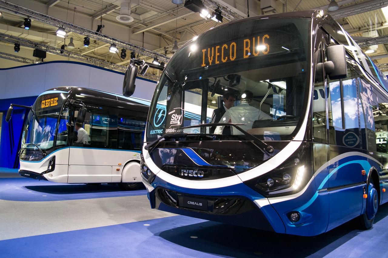 """Távolabb a francia Heuliez GX 337 E teljesen elektromos busz, """"akár"""" 300 km-es hatósugárral, 195 kW-os teljesítménnyel és 5 órás töltési idővel, előrébb a MABI formatervekre erősen hasonlító Iveco 18 méteres, csuklós, felsővezetékes töltésű villanybusza 250 kW teljesítménnyel"""
