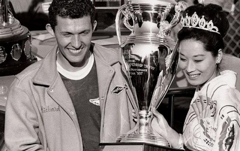 Miss Japán és Richard Petty a '64-es Daytona 500 után. A trófeán ott a szöveg: Japan, hála a nagy összeborulásnak