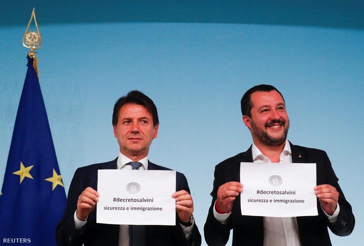 Giuseppe Conte (j), Olaszország miniszterelnöke és Matteo Salvini belügyminiszter kezükben tartanak egy papírt az új rendelet nevével a Chigi Palace-ban rendezett sajtókonferencián. 2018. szeptember 24-én