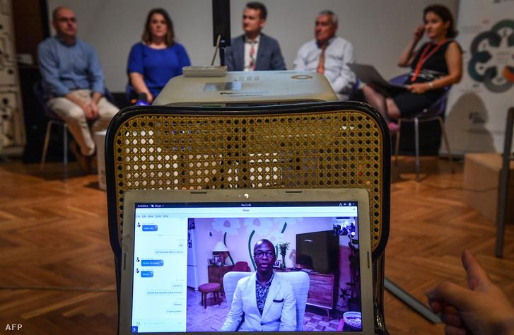 Adrian Coman (középen hátul) és apja videóhívás közben Clai Hamiltonnal (középen a laptop képernyőn) a bukaresti sajtótájékoztatón 2018 június 5-én
