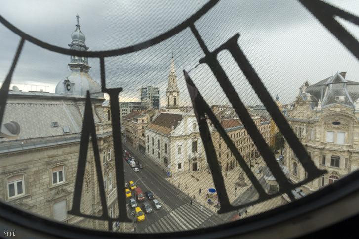 A Kossuth Lajos utca és a Ferenciek tere látképe középen az 1743-ban felszentelt barokk stílusú Belvárosi Ferences Templom a Párisi Udvar tetején lévő órán keresztül fényképezve 2018. július 11-én. Az év végére elkészül a Párisi Udvar Hotel Budapest épülete amely 110 szobás lesz 18 lakosztállyal valamint két tetőkertes körpanorámás luxuslakosztállyal.