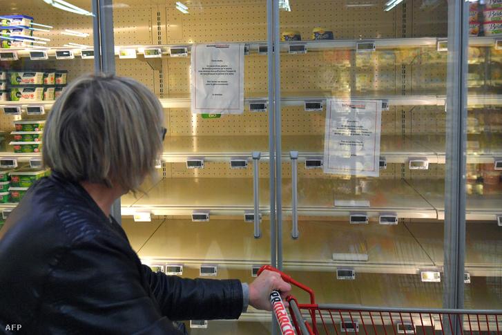 """""""Nyersanyaghiány miatt nem jelenleg nem lehetséges a vaj előállítása, ezért nem elérhető a termék."""" Olvasható egy bevásárlóközpont üres hűtőpolcán a felirat a franciaországi Rezében, 2017. október 25-én"""