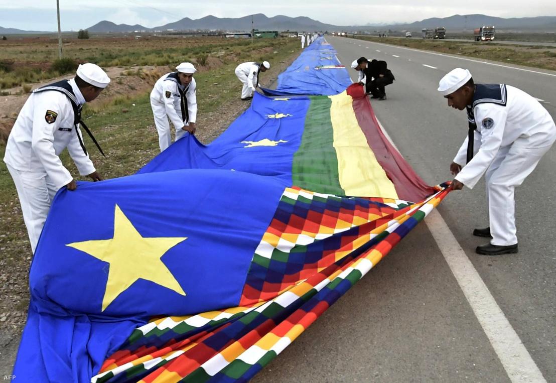Bolíviai tengerészgyalogosok a 200 kilométeres zászló kibontása közben, ami jelképesen összeköti La Pazt Oruroval 2018. március 10-én
