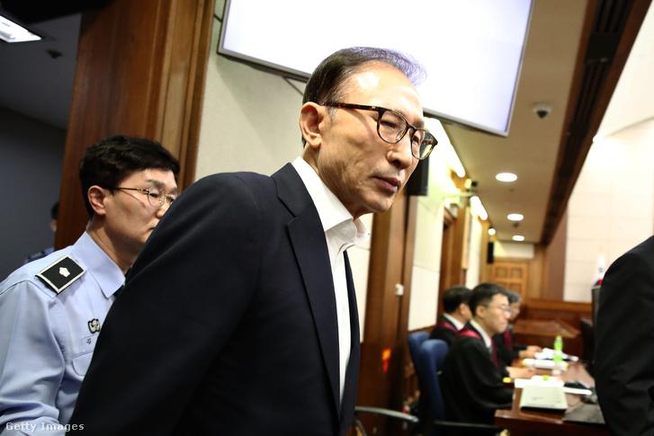 A többek között korrupcióval és hatalommal való visszaéléssel vádolt volt dél-koreai elnök egy szöuli bíróság tárgyalótermébe érkezik 2018. május 23-án.