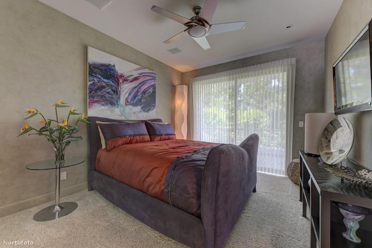 Az ágy fölötti nonfiguratív lila műalkotás valami egészen magával ragadó