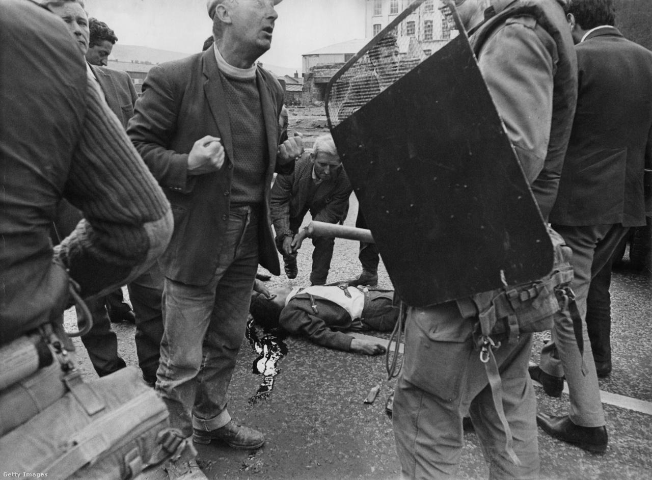 Súlyos sebesült fekszik az úton, miközben egy civil számon kér egy brit katonát az északír zavargások során 1969-ben.