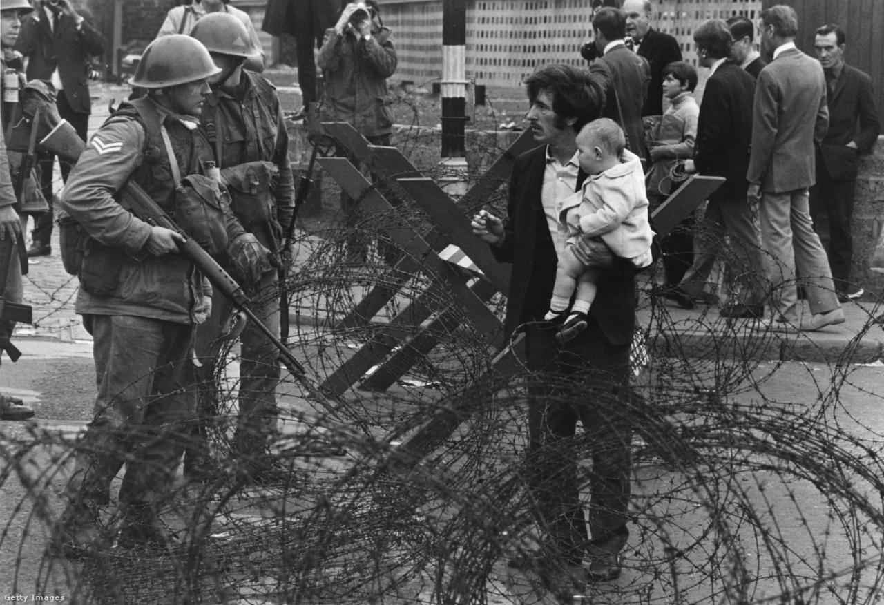 Brit katonák állítják meg a gyermekével átkelni szándékozó férfit a szögesdrótoknál. A férfi a belfasti Falls Road-on, a katolikus negyed barikádjánál próbálkozott (1969).