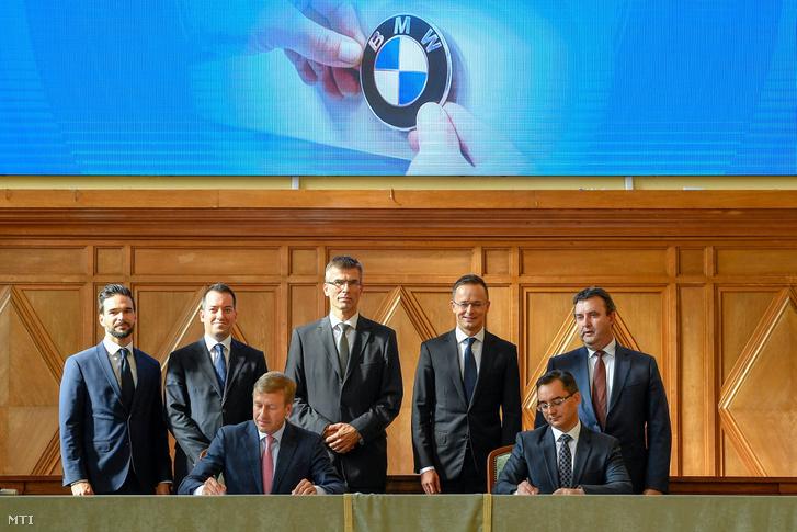Oliver Zipse, a BMW Group igazgatótanácsának gyártásért felelős tagja (elöl b) és Papp László (Fidesz-KDNP) polgármester (elöl j) aláírja a BMW debreceni gyárberuházásának támogatásáról szóló megállapodást a Debreceni Egyetemen 2018. október 12-én. Mögöttük Barcsa Lajos (Fidesz-KDNP) alpolgármester, Ésik Róbert, a Nemzeti Befektetési Ügynökség (HIPA) elnöke, Michele Melchiorre, a BMW gyár igazgatója, Szijjártó Péter külgazdasági és külügyminiszter és Palkovics László innovációs és technológiai miniszter (b-j).