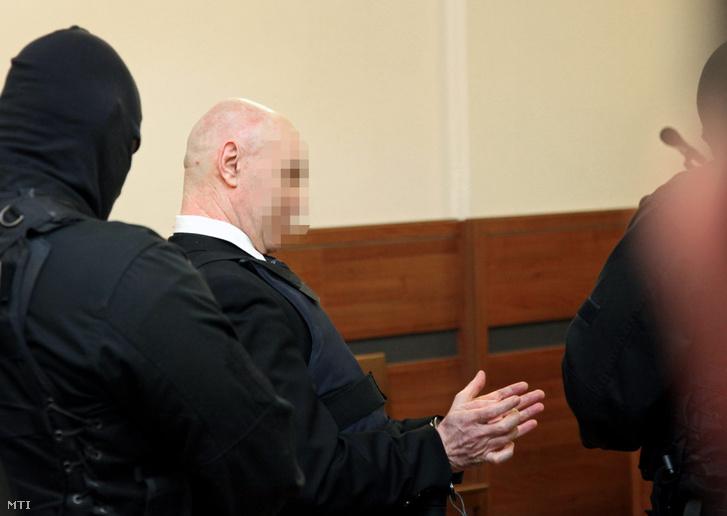 A büntetés-végrehajtás kommandósai kísérik be a Fővárosi Bíróság tárgyalótermébe a golyóálló mellényt viselő Jozef Rohácot, aki a vád szerint 1997-ben ismeretlen társaival megkísérelte felrobbantani Seres Zoltán vállalkozót.