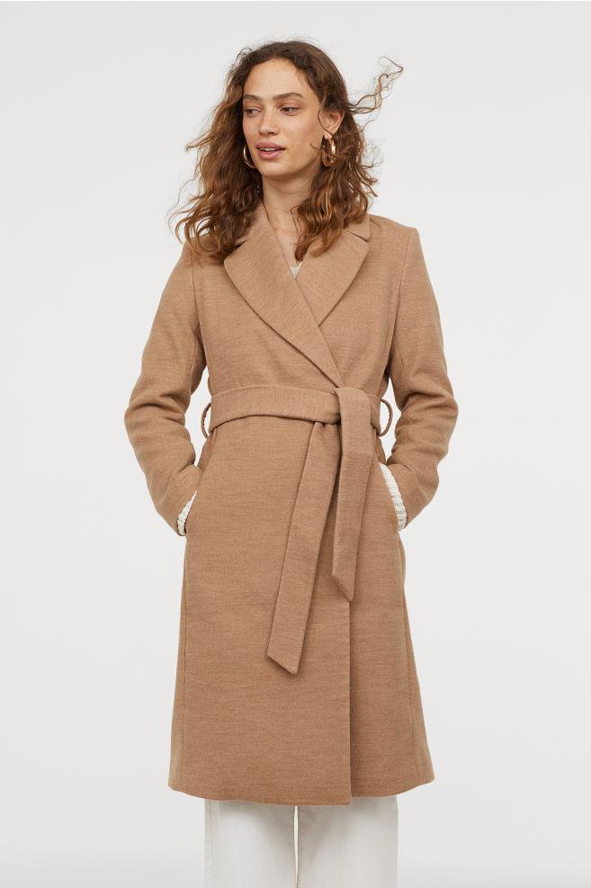 A H&M klasszikus, elegáns és nőies kabátja kötőjének köszönhetően karcsúsítja a derekat, és fazonja miatt az alakot is nyújtja. Drapp színben lesz a legdivatosabb. 14 990 forintért be is szerezheted.