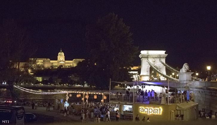 A zsúfolásig telt Raqpart nevű szórakozóhely, háttérben a Budavári palota és a Lánchíd.