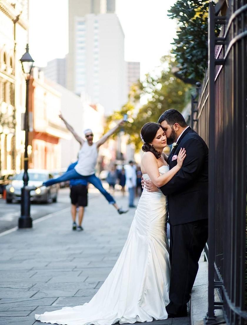 Minden megvan a tökéletes képhez: egy szerelmes ölelés és egy szép háttér egy vicces kedvű, ugró emberrel. A képeket visszanézve nem lehetett túl boldog a pár.