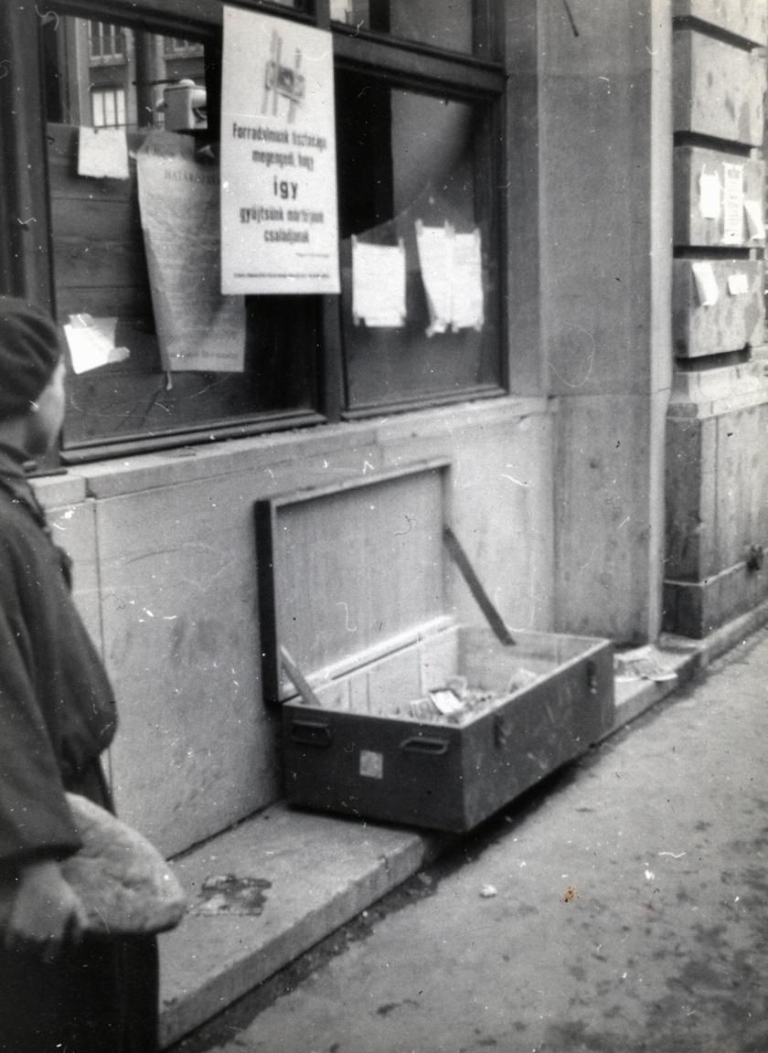 Budapest, V. kerület, a Kossuth Lajos utca és a Károly (Tanács) körút sarkán lévő gyógyszertár ablaka. Örizetlen pénzgyűjtő láda a Magyar Írók Szövetsége égisze alatt szervezett utcai pénzgyűjtő akció részeként.