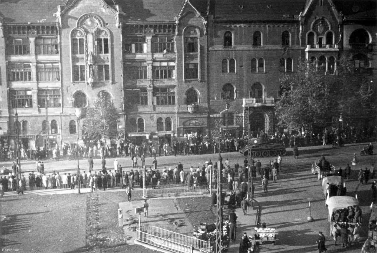 Emeleti kép a Móricz Zsigmond Körtérről., ahol többször is komoly harcok és barikádok voltak a forradalom napjaiban. Az út mellé sereglő emberek előtt valószínűleg itt egy magyar harckocsi megy el, jobb alul, a Karinthy Frigyes út felől felkelők érkeznek Csepel teherautókon. A felvétel november 3-án, egy nappal a szovjet bevonulás előtt készülhetett. Másnap a szemben lévő baloldali házat az oroszok rommá lőtték, a harcok után le kellett bontani.