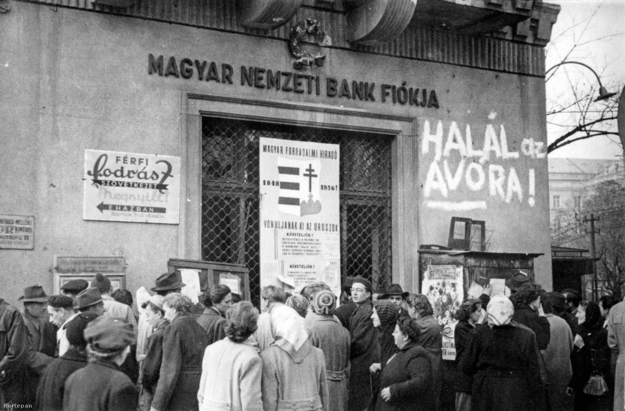 """Jobbra """"Halál az Ávóra"""", balra borkimérés, középen Magyar Forradalmi Híradó """"Vonuljanak ki az oroszok!"""" követeléssel és egy gyönyörű, kézzel festett Kossuth-címerrel: a Körtéren járunk, jobbra nyílik a Villányi út, háttérben a Kaffka épületrészlete. Egy kéz éppen felhívást ragaszt a fabodegára. Elolvasni nem tudjuk, de egyébként sok körtéri falragaszt ismerünk a rabruhás Rákositól sztrájkfelhíváson át a Takarodjatok!-ig - ezekből a FSZEK oldalán is látható egy válogatás."""