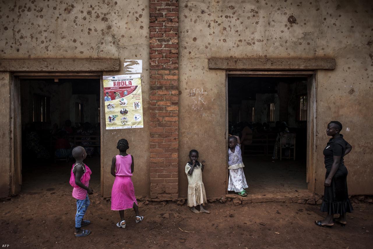 """Fiatal kongói lányok az ebola tüneteit magyarázó plakát előtt.Oly Ilunga Kalenga kongói egészségügyi miniszter azonban vasárnap arról beszélt, hogy az egészségügyi dolgozók és a civilek ellen elkövetett támadások a környék irányításáért harcoló militáns csoportok között eddig meghiúsították a járvány megállítását. """"Emiatt a világon egyetlen járvány sem ennyire bonyolult, mint amivel most szembenézünk"""" – mondta Kalenga."""