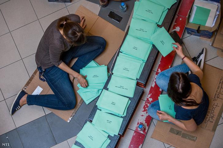 Az átjelentkezéssel szavazók szavazatait tartalmazó borítékokat válogatják a Nemzeti Választási Iroda munkatársai.