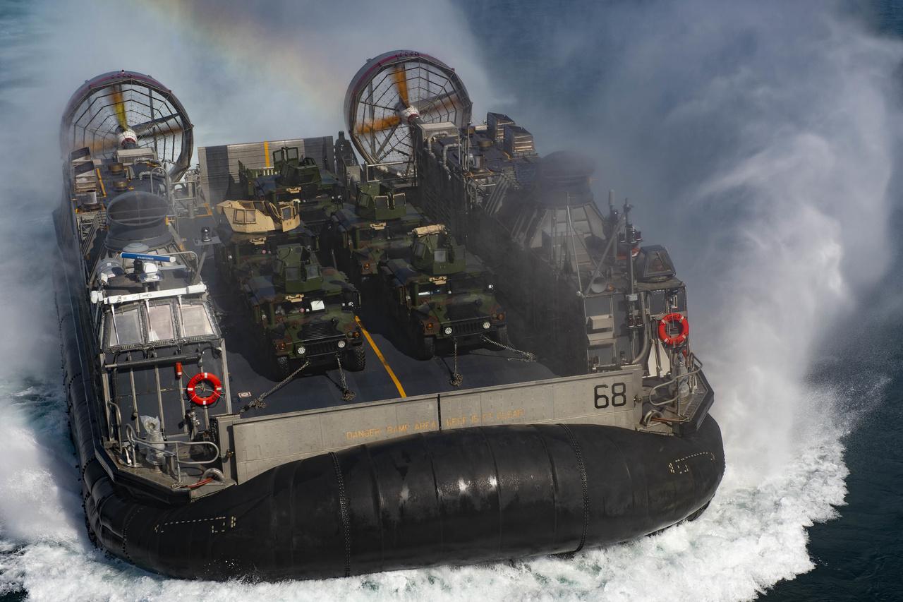 Az Iwo Jima egyik légpárnás kétéltű partraszálló hajója visz páncélozott terepjárókat a hajó rakterébe.