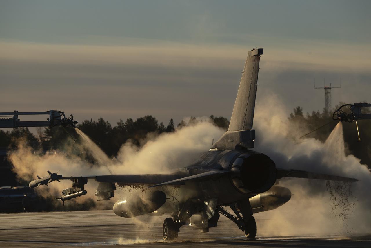 Az amerikai légierő egyik F-16 Fighting Falcon vadászgépét jégtelenítik gyakorlat előtt egy svédországi repülőtéren.