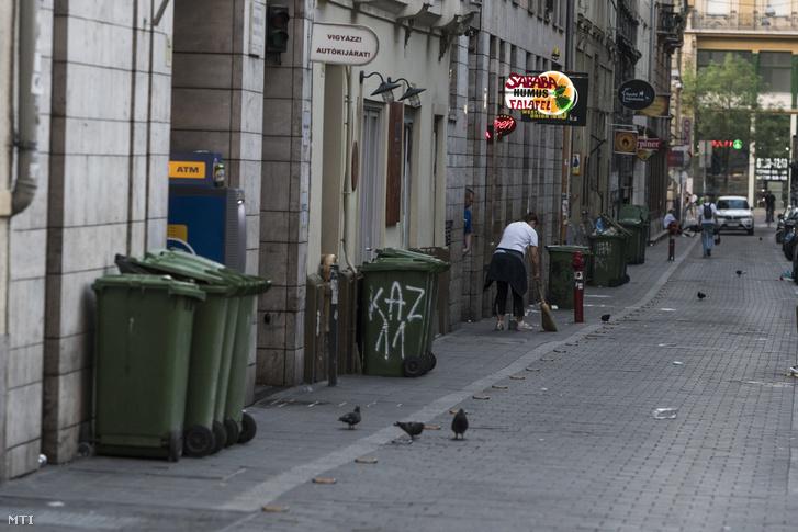 Takarító söpör a budapesti Kazinczy utcában 2018. május 28-án hajnalban.