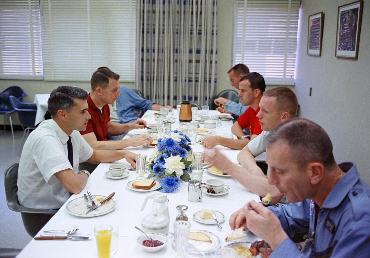 Fotó a NASA-archívumából: a Gemini-8 küldetés legénysége (Neil Armstrong, jobb oldalt alulról a 2., és David Scott, az asztal bal oldalán, alulról a 2., piros pólóingben) reggelizik steaket és tojást a start napján. Csatlakoztak hozzájuk fess űrhajóstársaik (Donald Slayton, Curtis Michel, Walter Cunningham, Alan Shepard és Roger B. Chaffee).