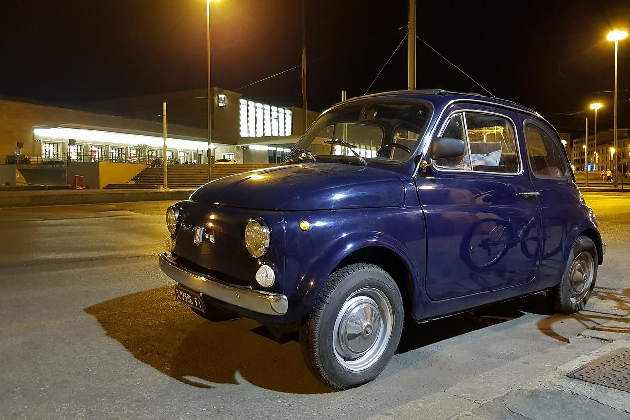 Dél-olasz túránk egyéjszakás firenzei villámlátogatással indult, ahol legalább 150 métert kellett sétálni, hogy egy eladó, egészen szép állapotban lévő klasszikus Fiat 500-ra akadjunk. Azért ez itt nem túl nagy mutatvány, mivel 1957 és 1975 között majdnem négymillió készült a kis farmotoros, vászontetős aszfaltpattanásból. A központi pályaudvar előtti sápadt, sárgás fényben kellette magát, bár az összképen a kissé ormótlan, műanyag házas visszapillantó és egyéb apróságok rontottak kissé