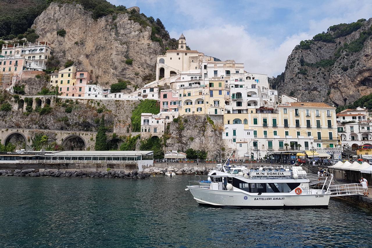 Amalfi kikötője. Maga a városka véleményem szerint kevesebb időt érdemel, mint a pezsgő, izgalmas Positano, ám a kettő közötti hajóutat vétek kihagyni. Ezek elfogadható sűrűséggel járnak, vízen is el lehet jutni idáig, akár Nápolyból is, de Capri szigete is egyszerűen elérhető innen. Brutális sziklák, rejtett öblök, eszméletlen épületek, tényleg a világ egyik legszebb partvidéke