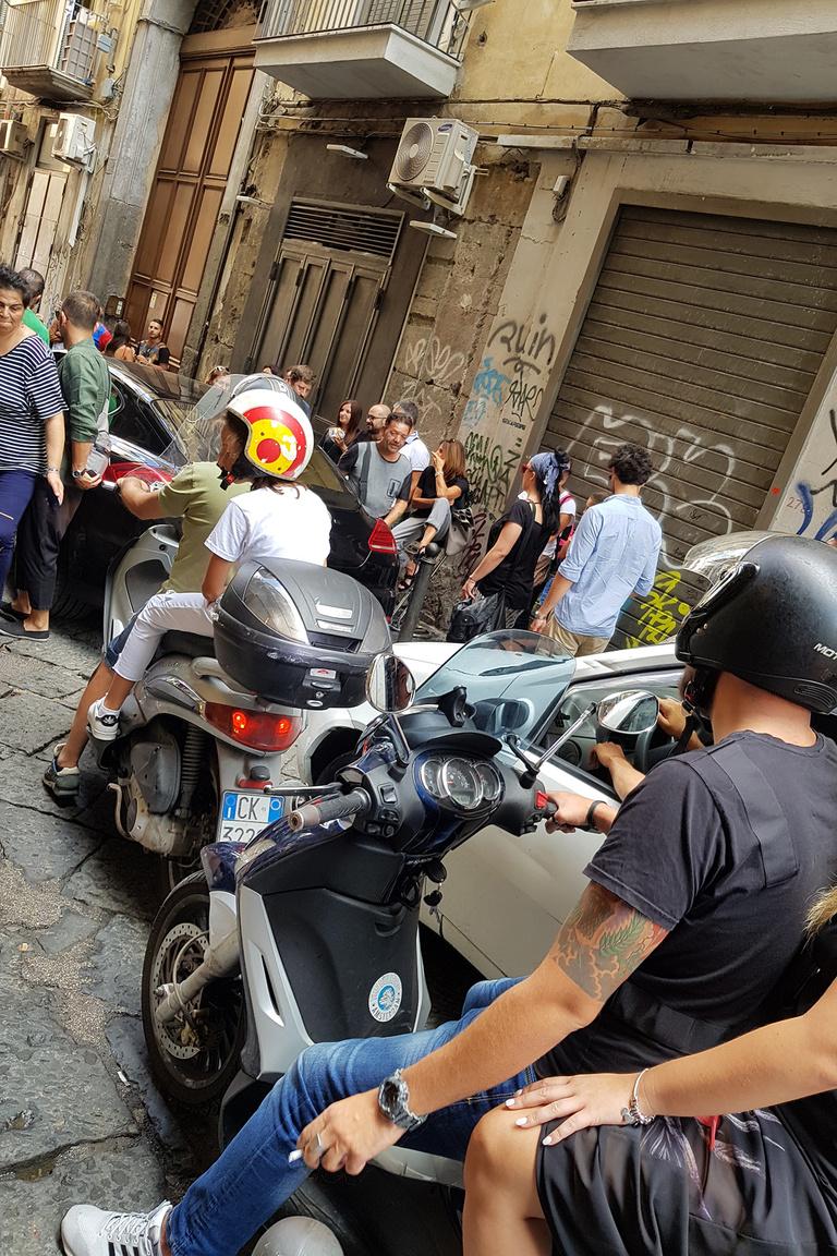 Nápoly sűrűjében. A koszos, szűk utcákban egymást kerülgetik a járókelők, motorosok, autósok olyan helyeken is, ahol ezekből egy is sok lenne. Ráadásul a legtöbbször egymásról látványosan nem vesznek tudomást, így nem árt minden másodpercben észnél lenni, mert könnyen fellökik a csóri járókelőt. Ilyen szempontból nem sokban különbözik a kultúra a közel-keleti országokhoz képest