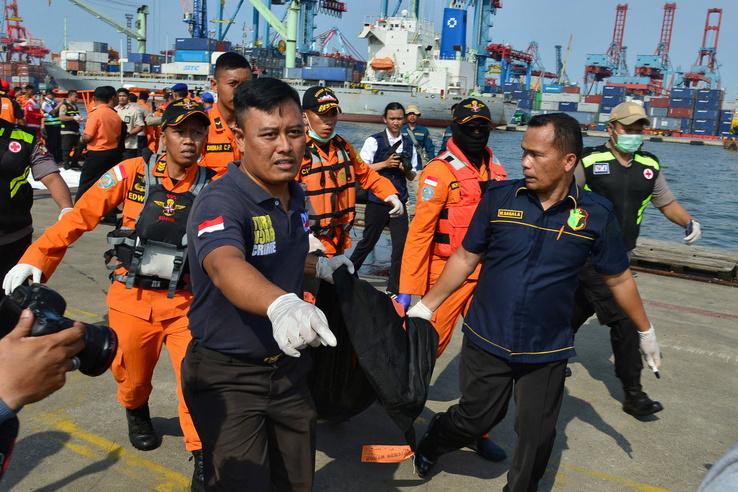 A mentőcsapat tagjai a gép egyik utasának holttestét viszik Jakarta kikötőjében.