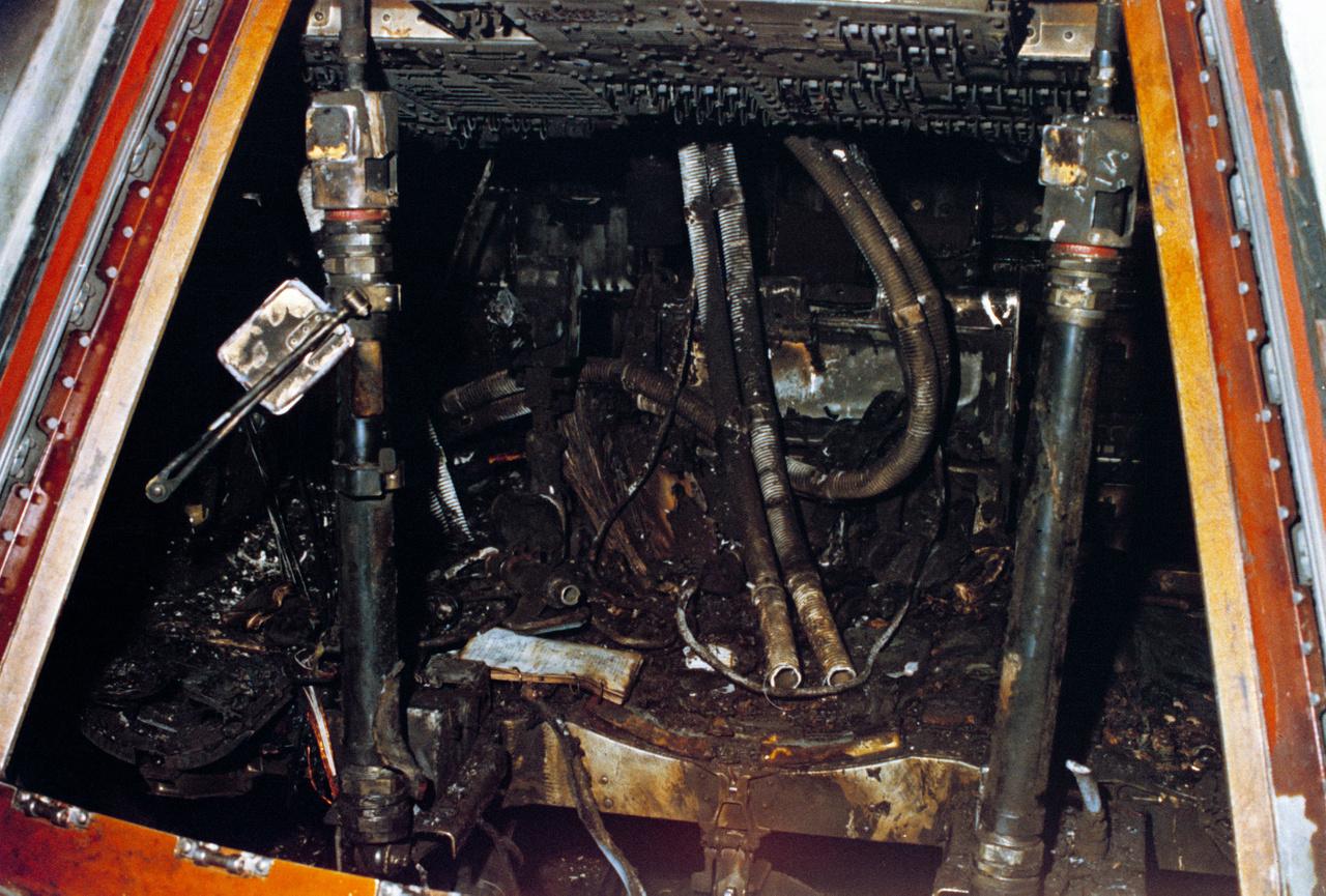 Egy megrázó NASA fotó. A kiégett parancsnoki modul belseje a tragédia másnapján. A tűz kiindulópontja feltehetően egy vagy több zárlatos vezeték volt, az enyhén túlnyomásos, oxigédús kabin belsejében a lángok villámgyorsan terejedtek, minden éghető anyagot elemésztve, Az űrhajósok pár pillanat alatt bekövetkező halálát füstmérgezés okozta.
