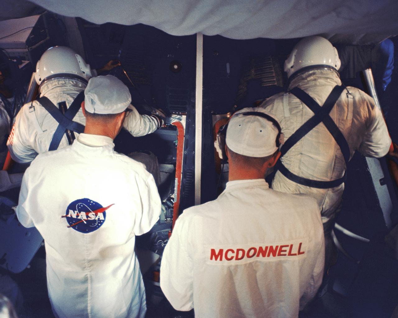 A NASA és a McDonnell technikusai segítenek a két űrhajósnak beszállni a Gemini-8 űrhajóba a start előtt a Kennedy Űrközpont 19-es startállásán. (35 mm-es diafilmkocka, 1966. március 16., NASA-azonosító: 104-KSC-66C-1852)