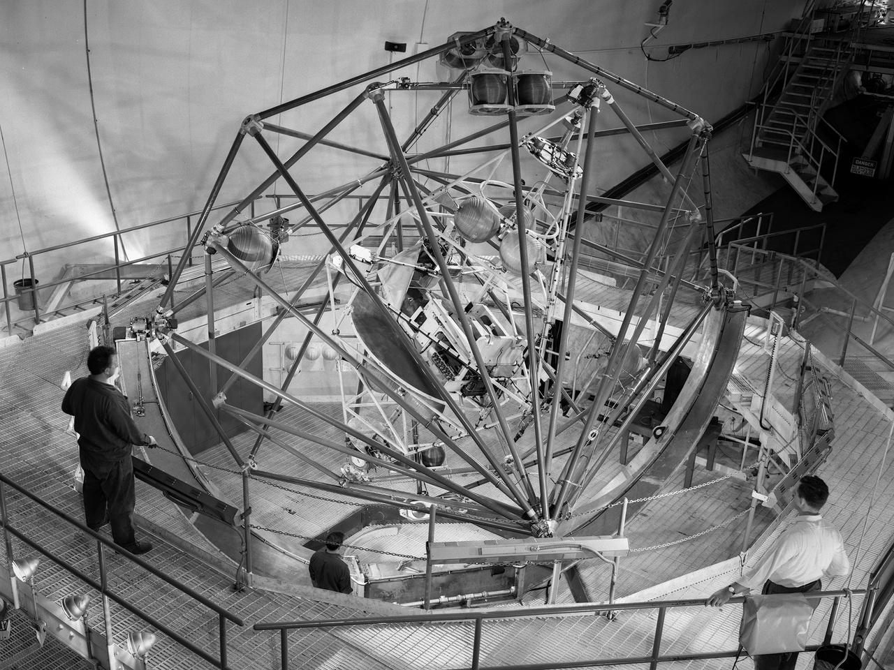 """A hatvanas évek elején így nézett ki a MASTIF, azaz a Multi-Axis Space Test Inertial Facility a NASA Lewis kutatóközpontjában. A több tengelyű forgással való megbírkózás azért volt létfontosságú, mert amennyiben nem a megfelelő pozícióban (azaz hőpajzzsal előre, a landolási ív irányában) érkezik az űrhajó a légkörbe, akkor megsemmisül a légköri súrlódás közben termelődő hő hatására, éppen ezért a MASTIF-ot már az űrprogram legelejétől, a Mercury űrhajósok kiképzésénél is használták. A vezérléstől függően percenként akár 50 fordulattal is pöröghettek a pilóták, akiknek kis nitrogénfúvókákkal kellett a pörgés ellenében stabilizálni a szimulátor """"fülkéjét""""."""