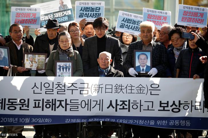 Lee Choon-sik, a japán gyarmati időszak egyik kényszermunkás áldozata (középen) és tüntetők akik az elhunyt Dél-Koreai kényszermunkások képeit tartják a kezükben 2018. október 30-án, Szöulban