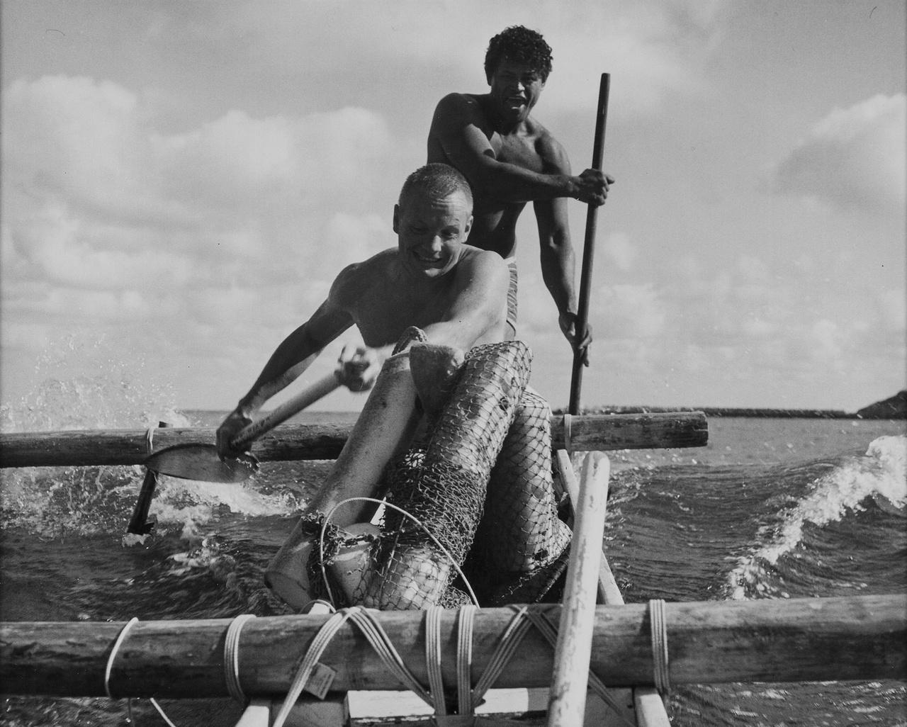 Armstrong egy katamarán csónakon evez szemmel láthatóan teljes erőbedobással.