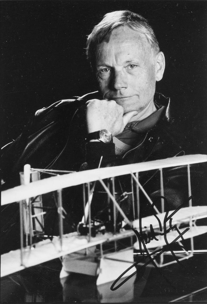 Egy ugyancsak ritka portré, családi célra készült, nem hivatalos NASA-fotó (Armstrong 1971-ben vonult vissza a NASA-tól, a civil életben egy sor amerikai cégnek lett a szóvivője, igazgatósági tagja). A nyolcvanas évekből származó dedikált képen Armstrong a Wright-testvérek első repülőgépének modelljével pózol