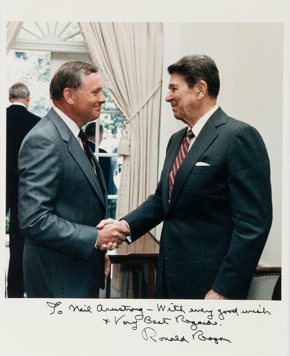 Armstrong kezet ráz az amerikai elnökkel, Ronald Reagannal. 1986. június 9-i, hivatalos, elnök által dedikált fehér házi fotó. Az elnök ezen a napon adta ki a Challenger űrsikló hét halálos áldozattal járó katasztrófáját kivizsgáló Rogers-bizottság jelentését. Armstrong volt a bizottság alelnöke, a feladatra maga Reagan kérte fel.