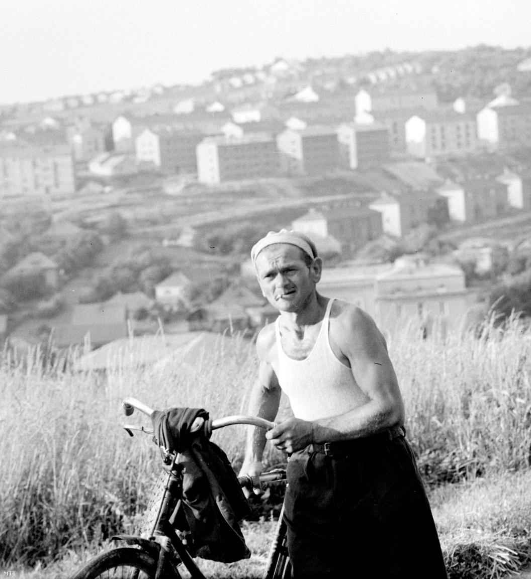 Egy férfi hazafelé tart a munkából kerékpárjával Komlón (1960)