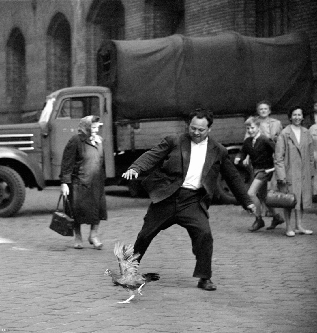 Egy elszabadult csirkét próbál megfogni egy férfi a Nagycsarnok mellett. (1963)