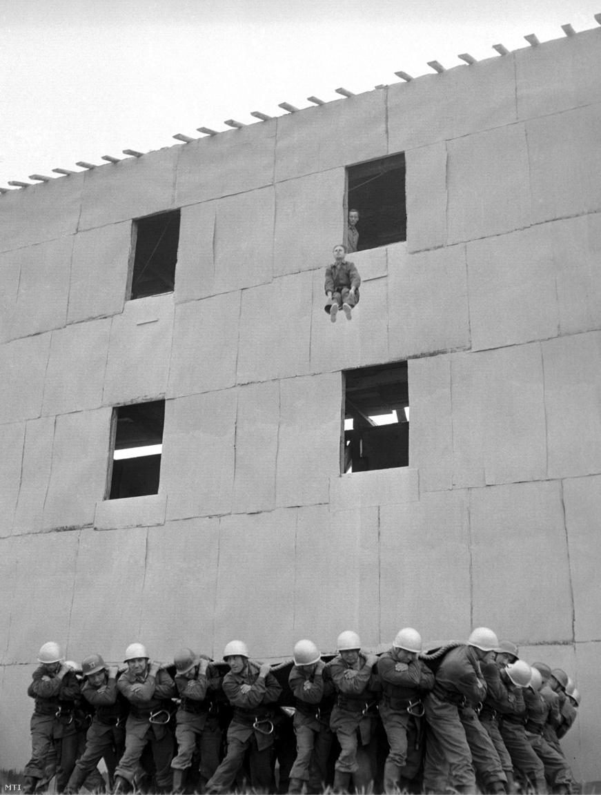 Egy tűzoltó mentőponyvába ugrik az Állami Tűzoltóság főpróbáján. (1958)