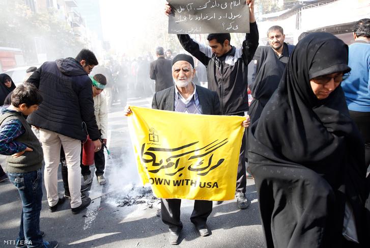Le az USA-val feliratú transzparens az egyik tüntető kezében az Egyesült Államok volt teheráni nagykövetségének épülete előtti megmozduláson a nagykövetség elfoglalásának 39. évfordulóján 2018. november 4-én.