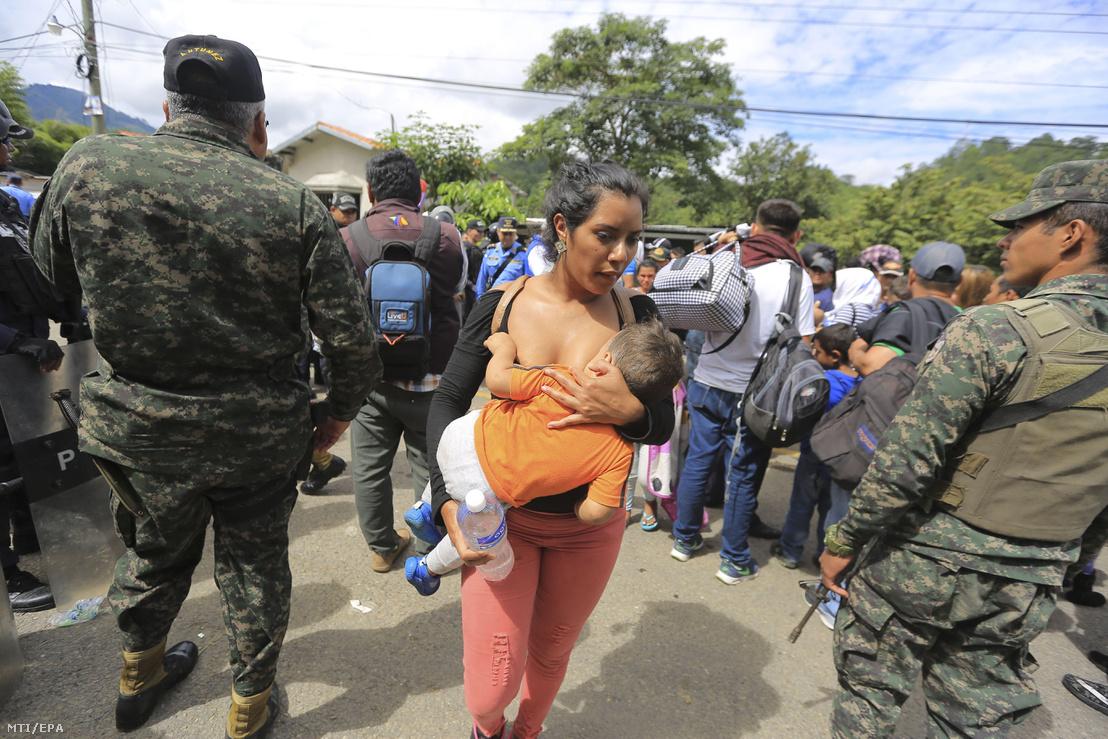 Gyermekét szoptató hondurasi kivándorló és katonák a guatemalával határos Agua Caliente településnél 2018. október 18-án.